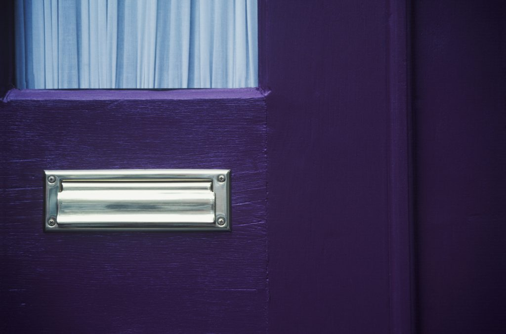 A purple door with mail slot to illustrate What Are HOAs And How Do They Benefit Your Community blog post.